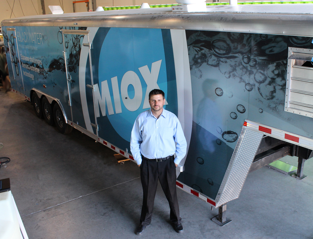 MIOX Chief Technology Officer, Justin Sanchez, stands next to the Blackwater mobile produced water treatment system.